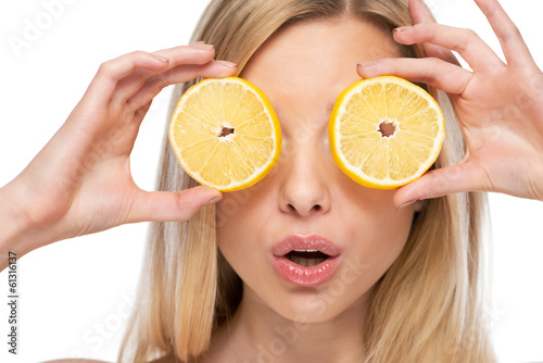 Young woman holding lemon slices in front of eyes