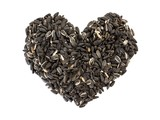 Sunflower seeds shaped as a heart on white background