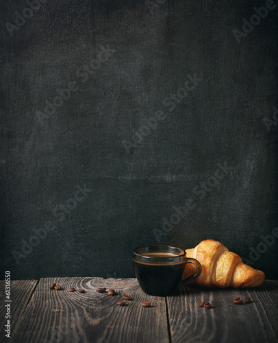 coffee and croissant on blackboard background. copy space
