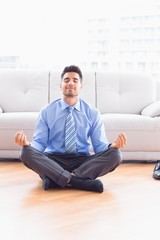 Handsome businessman meditating in lotus pose on the floor