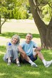 Mature couple sitting with water bottles at park