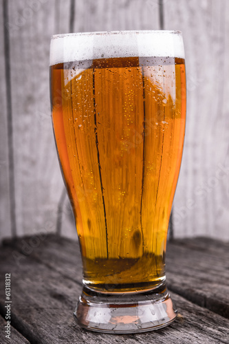 Glass of cold beer on wood background