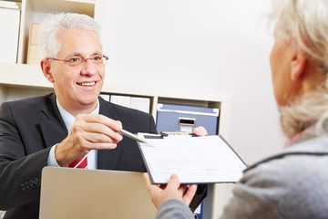 Business man giving senior woman contract