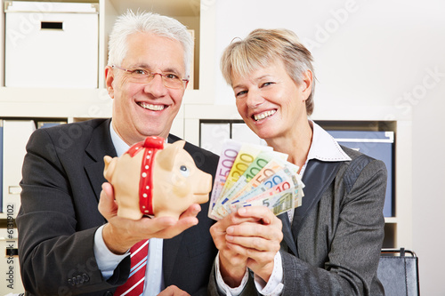 Business people holding Euro money and piggy bank
