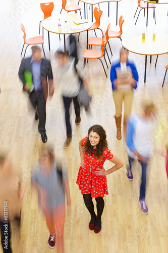 Female Pupil In Classroom Surrounded By Moving Students