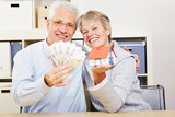 Happy elderly couple with house and money