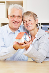 Happy senior couple holding house in hands