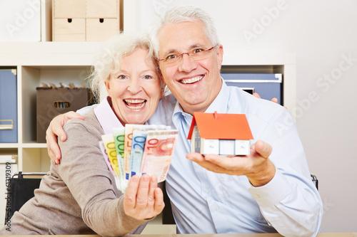 Fototapeta Happy elderly couple with Euro money and house
