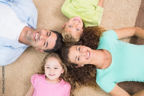 canvas print picture Happy family lying on the rug in a circle