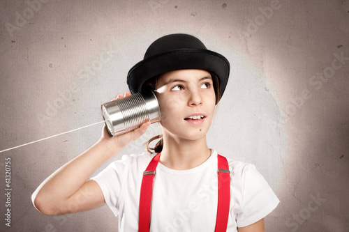 little girl using a can as telephone