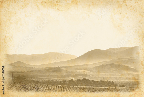 Ancient page with vineyard and mountain landscape.