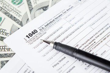 Tax forms with dollar bills