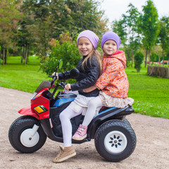 Two Little beautiful sisters sitting on toy motorcycle in green