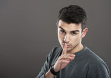 Portrait of a guy making a silence gesture, gray background