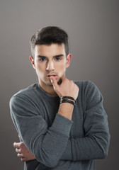 Studio portrait of a thoughtful young man looking at camera