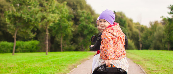 Portrait of little cute girls ride a motorbike outdoors