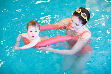 Little baby in an early swimming class