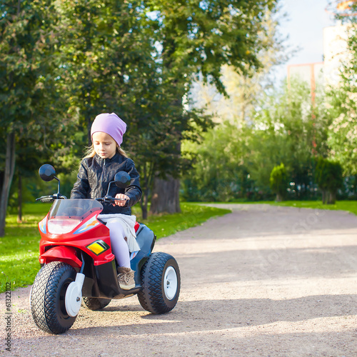 Adorable little girl riding a children's bike