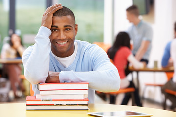 Male Student Studying In Classroom With Books