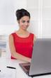 Junge erfolgreiche indische Geschäftsfrau sitzend vor dem PC