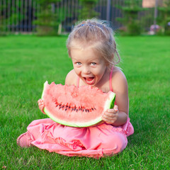 Little adorable girl with a piece of watermelon in hands
