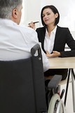 Businesswoman interviewing disabled job candidate in his office