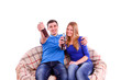 Young couple sitting on a couch and drinking a soda