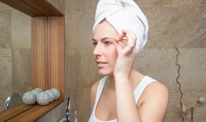 Portrait of girl plucking eyebrows with tweezers