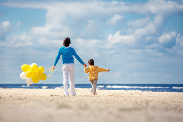 Family with yellow balloons on the beach