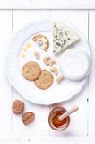 Cheese plate. Various types of cheese with honey and nuts.