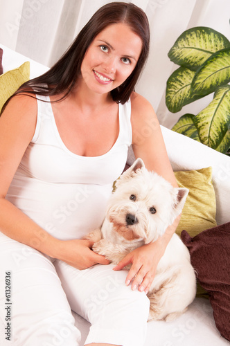 Happy pregnant woman with west highland white terrier relaxing o