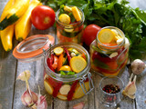 Preparing preserves of pickled zucchini, pepper and tomatoes in