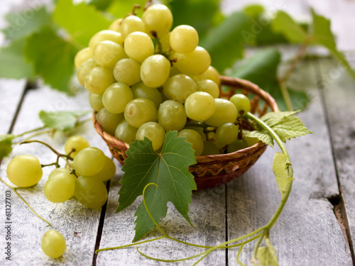Fresh white grape in basket on wooden background