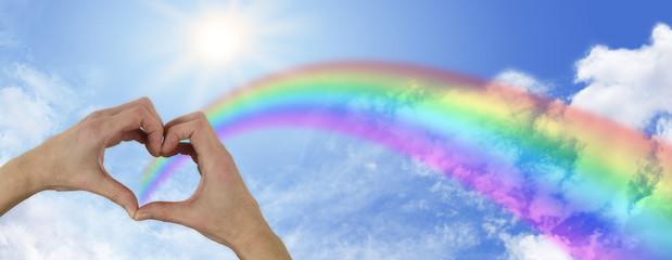 heart hands and beautiful sunny rainbow