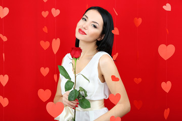 Attractive young woman with rose on Valentine Day