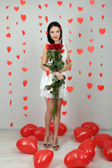 Attractive young woman with roses and balloons in room