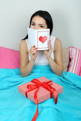 Beautiful woman with gift in bed on Valentine Day