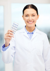smiling young doctor in cabinet with pills