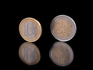 Euro coins standing on black