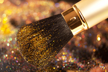 Closeup on makeup golden brush and shining powder
