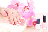 Beautiful woman hands with french manicure and flowers