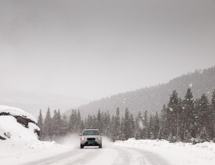 car driving along snow covered road in a snowstorm