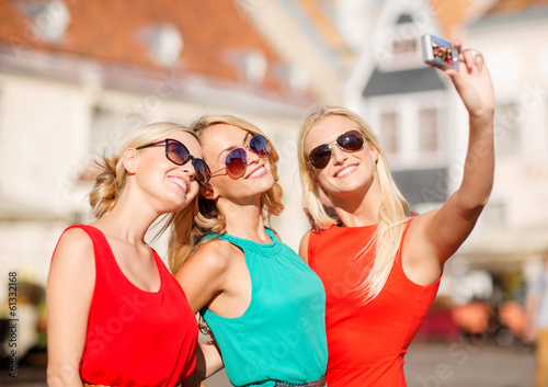 three beautiful girls taking picture in the city