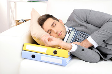 Elegant young businessman sleeping on sofa, at home