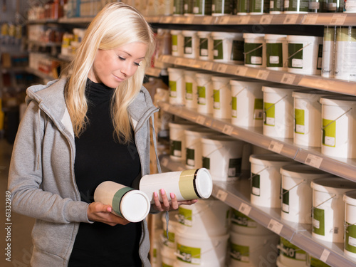Woman deciding between product in hardware store