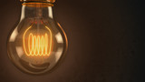 Close up of an illuminated vintage hanging light bulb over dark