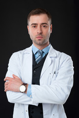 Mature Serious male doctor with crossed arms isolated on black b