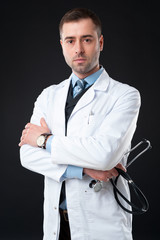 Serious male doctor holds stethoscope in hand isolated on black