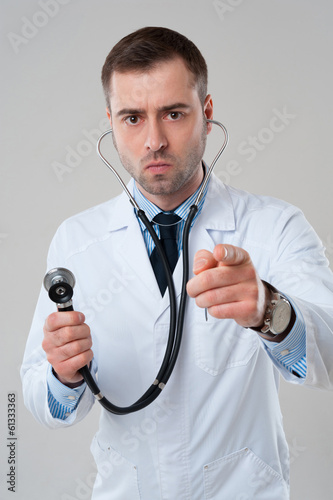 Serious man doctor holds stethoscope in hand and pointing at cam