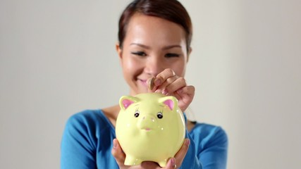 asian girl showing piggybank and euro coin